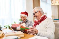 Happy Senior Couple Opening Christmas Presents royalty free stock photos