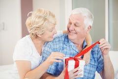 Happy senior couple opening gift Royalty Free Stock Photography