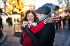 Senior couple on an outdoor Christmas market. Happy senior couple on an outdoor Christmas market, exchanging presents. Winter time Royalty Free Stock Photos