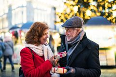 Senior couple on an outdoor Christmas market. Happy senior couple on an outdoor Christmas market, exchanging presents. Winter time Royalty Free Stock Photo