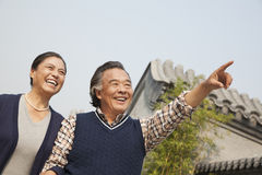 Happy senior couple outdoors pointing by traditional building in Beijing Stock Photo