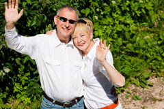 Happy senior couple outdoors waving hands Royalty Free Stock Image