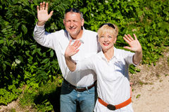Happy senior couple outdoors waving hands Royalty Free Stock Photography
