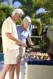 Happy Senior Couple Outside Cooking on A Barbecue. Happy senior men and women couple outside cooking kebabs on a summer barbecue stock photo