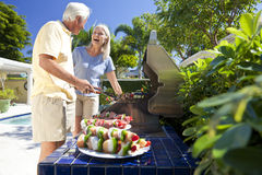 Happy Senior Couple Outside Cooking on A Barbecue. Happy senior men and women couple outside cooking kebabs on a summer barbecue Royalty Free Stock Photos