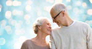 Happy senior couple over blue holidays lights Royalty Free Stock Photos
