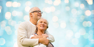 Happy senior couple over blue holidays lights Stock Photography