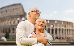 Happy senior couple over coliseum in rome, italy. Family, tourism, travel and people concept - happy senior couple over coliseum in rome, italy Royalty Free Stock Images