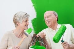 Happy senior couple painting their house green stock photo