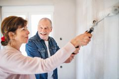 Senior couple painting walls in new home, relocation concept. royalty free stock image