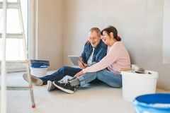 Senior couple painting walls in new home, using tablet. Relocation concept. royalty free stock photo