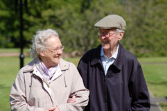 Happy senior couple in park. A senior couple laughing while strolling in the park Stock Image