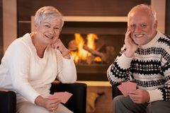 Happy senior couple playing cards at home Stock Images