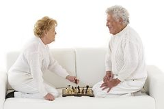 Happy senior couple playing chess Stock Images