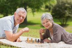 Happy senior couple playing chess at park Stock Photos