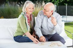 Happy Senior Couple Playing Dominoes At Porch Stock Images