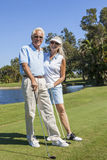 Happy Senior Couple Playing Golf. Happy senior men and women couple together playing golf on a course near a lake royalty free stock image