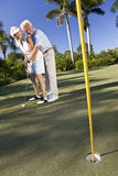 Happy Senior Couple Playing Golf & Putting. Happy senior man and woman couple together playing golf putting on a green together Stock Photo