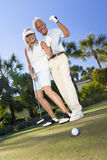 Happy Senior Couple Playing Golf Putting on Green. Happy senior men and women couple together playing golf and putting on a green, celebrating the ball going in royalty free stock images