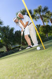 Happy Senior Couple Playing Golf Putting on Green. Happy senior men and women couple together playing golf and putting on a green, the men is teaching the women royalty free stock photo
