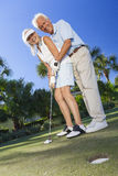 Happy Senior Couple Playing Golf Putting on Green. Happy senior men and women couple together playing golf and putting on a green, the men is teaching the women royalty free stock photos