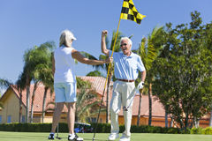 Happy Senior Couple Playing Golf Together. Happy senior men and women couple together playing golf celebrating on a putting green together stock image