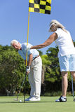 Happy Senior Couple Playing Golf Together. Happy senior men and women couple together playing golf putting on a green together stock photos