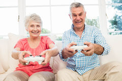 Happy senior couple playing video games Stock Photos