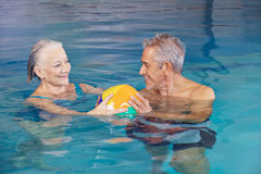 Happy senior couple playing water ball Stock Images