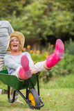 Happy senior couple playing with a wheelbarrow Stock Photos