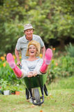 Happy senior couple playing with a wheelbarrow Stock Image