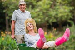 Happy senior couple playing with a wheelbarrow Royalty Free Stock Photo