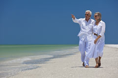 Happy Senior Couple Pointing To Sea on Beach. Happy senior man and woman couple walking together looking out to sea on a deserted tropical beach with bright