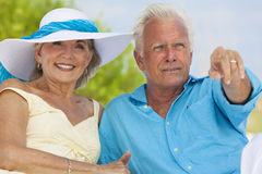 Happy Senior Couple Pointing on A Tropical Beach. Happy senior man and woman couple sitting together pointing out to sea on a deserted tropical beach Stock Photos