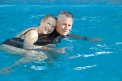 Happy senior couple in pool stock image