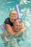 Happy senior couple in pool. Beautiful happy senior couple having fun in an outdoor swimming pool Stock Images