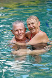 Happy senior couple in pool. Beautiful happy senior couple having great loving and fun together time in an outdoor swimming pool Stock Photo