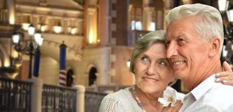 Portrait of happy senior couple posing against blurred cityscape background royalty free stock photos