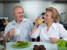 Happy senior couple preparing healthy vegetarian breakfast with fruits and vegetables - Old cheerful people taking care stock images