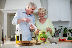Happy senior couple preparing vegetable salad. In kitchen Stock Photo