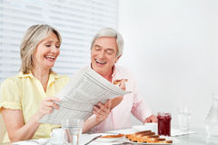 Happy senior couple reading Stock Images