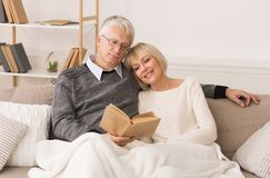 Happy senior couple reading book, spending time together stock photo