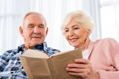 Happy senior couple reading. Book together royalty free stock photo