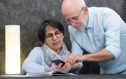 Happy senior couple reading message to smartphone stock photo