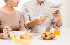 Happy senior couple reading newspaper at breakfast Royalty Free Stock Images