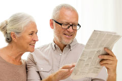 Happy senior couple reading newspaper at home Stock Photos