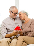 Happy senior couple with red gift box at home Stock Photo