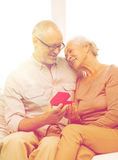 Happy senior couple with red gift box at home Royalty Free Stock Image
