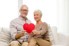 Happy senior couple with red heart shape at home Royalty Free Stock Photography