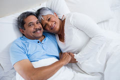 Happy senior couple relaxing on bed in bedroom Royalty Free Stock Photos
